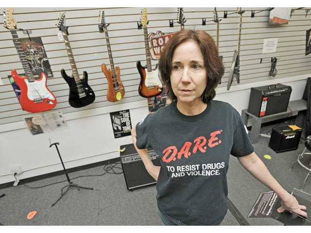 Lori Martinez stands near a guitar display at World Music in Newhall, on Thursday, which has closed after many years in the community. The store closed its doors forever last Saturday.