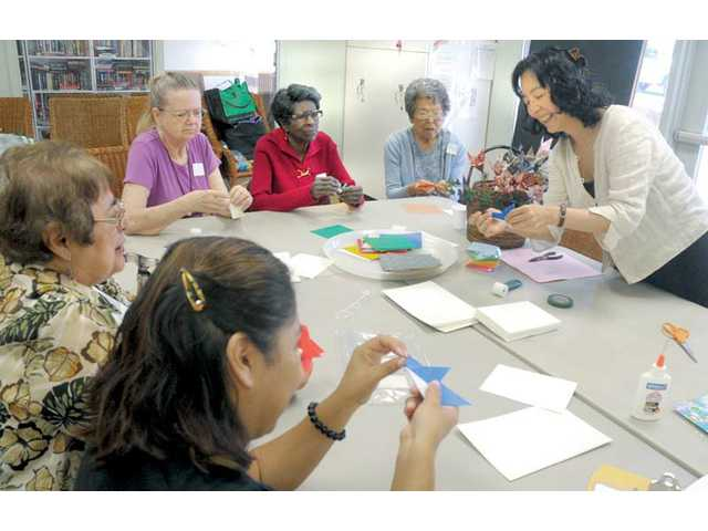 Teacher Shuko Shikauchi Nielsen, right, instructs the class on how to fold a winter bird out of paper at an origami class at the SCV Senior Center in Newhall on Friday.