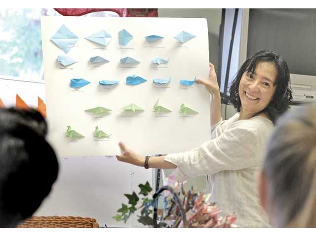 Shikauchi Nielsen presents a board demonstrating the steps to fold various animals out of paper at an origami class.