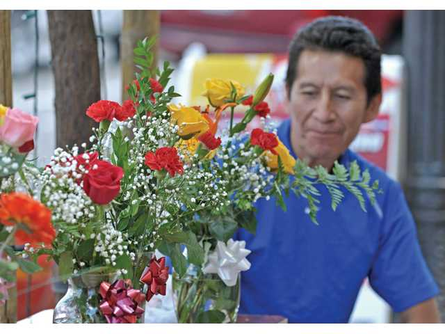 Aurelio Cuervo waits next to flower arrangements for sale in front of Victoria's Rental in Old Town Newhall on Tuesday.