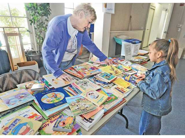 Angelique Oliveros, 6, right, is assisted by Mary Johnston as she picks out free books at the Angel Food Ministries distribution held at Valencia United Methodist Church in Valencia.