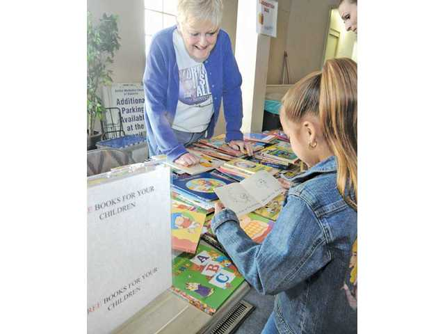 Angelique Oliveros, 6, right, is assisted by Mary Johnston as she picks out free books at the Angel Food Ministries food distribution held at the United Methodist Church in Valencia.