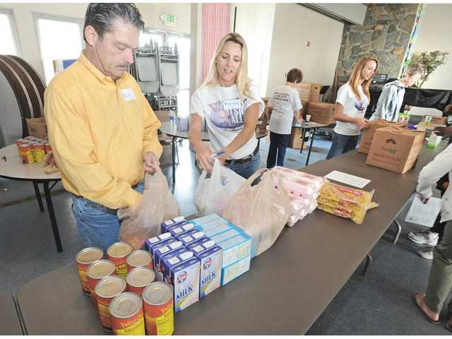 Ellis Anderson, left, and Karen Ewart join other volunteers as they pack boxes of food for recipients at an Angel Food Ministries distribution in April. Angel Food provides families of four a monthly box of food that can help feed the family for a week at a cost of $31.