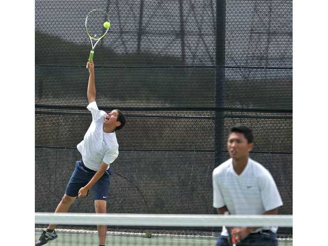 West Ranch's doubles player Ali El-Arabi, left, serves as partner Wayne Moses waits on Friday at West Ranch High.