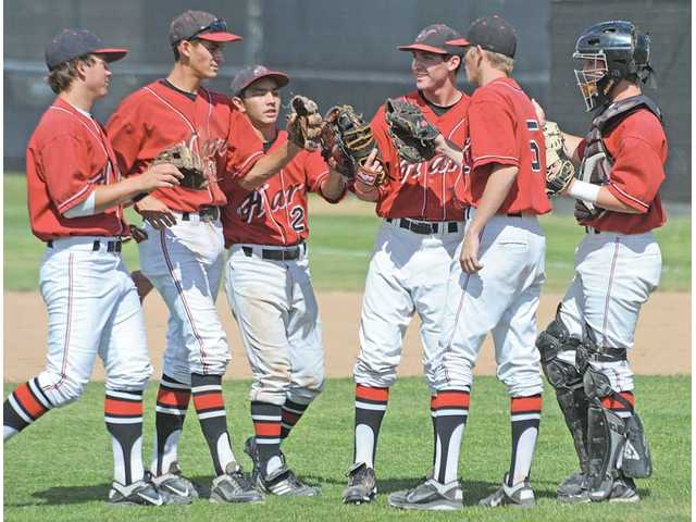 Hart High baseball players congratulate each other after getting out of the second inning Friday at Hart High.