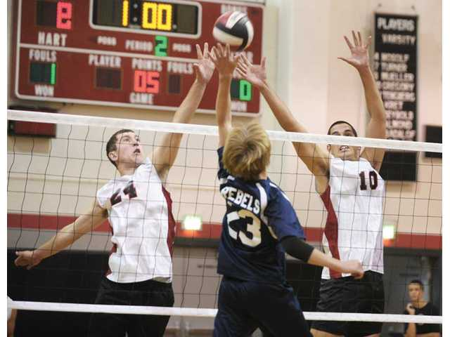 Hart High's Cody Seybold (24), left, and Taylor Gregory (10), right, block a shot by Nick Bauer (23) of Quartz Hill during  Hart High's 3-1 victory on Tuesday.