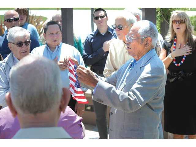 Ed Bolden holds a U.S. flag as attendees say the Pledge of Allegiance during a dedication ceremony for a plaque for fallen soldier Spc. Rudy A. Acosta in the Rotary Garden at the George Caravalho Sports Complex in Santa Clarita on Wednesday.