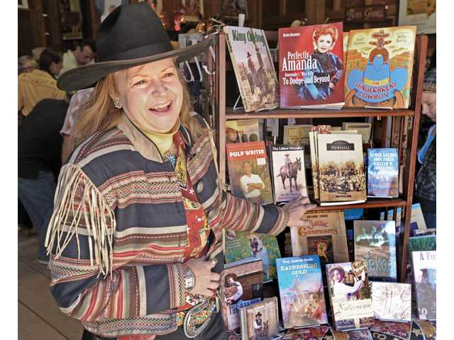 Bobbi Jean Bell stands next to a display of Western literature. The Bells opened OutWest in July 2009.