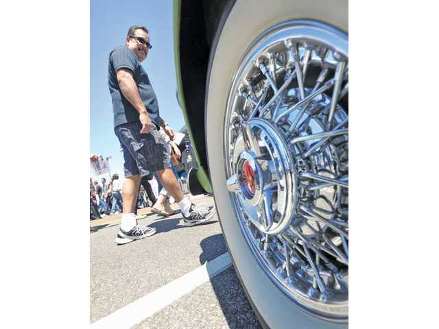 An attendee walks past a 1950s Ford Thunderbird, one of the hundreds of cars that were on display. The event was a first of its kind on Creekside Road.