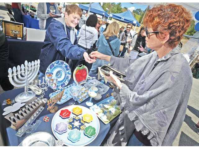Taffiney Goldberg, right, buys a toy dreidel from volunteer Jodi Liss-Monteleone at the Congregation Beth Shalom-Santa Clarita booth at the SCV Jewish Food and Cultural Festival at College of the Canyons on Sunday.