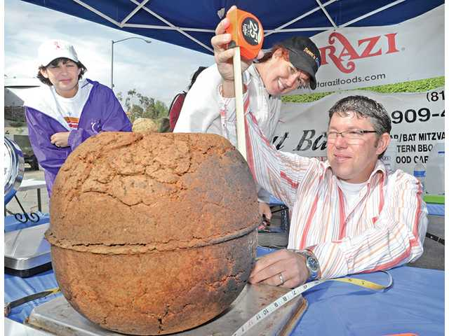 Sandi Henderson, left, and chef Dawn Walker, center, look on as licensed surveyor Misha Georgevitch takes a measurement of a giant falafel for a Guinness World Record.