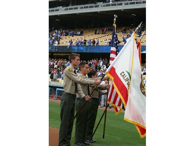 Members of the L.A. County Sheriff's Explorer Group based in Santa Clarita served as the color guard for SCV Dodger Day at Dodger Stadium on Saturday. Flag bearers Trevor Kirk (left) and Mike Thompson (center) are drill instructors, while Elizabeth Casique (right) is a drill instructor trainee.