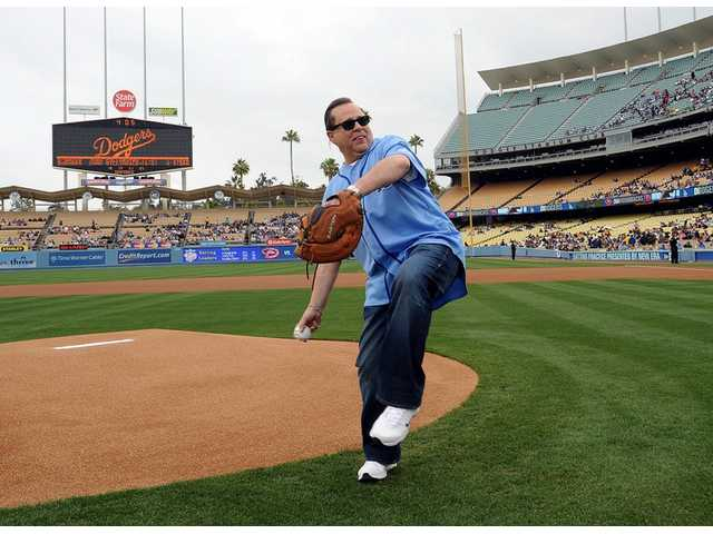 ACTION chief Cary Quashen winds up to throw the ceremonial first pitch to catcher Jim Ventress of the Boys & Girls Club on SCV Dodger Day at Dodger Stadium on Saturday,