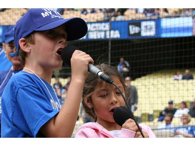 "Future broadcasters Ryan Downing (left) and Ryan Vasquez (right) loudly announce ""It's time for Dodger baseball!"" over the stadium P.A. to start the game at Dodger Stadium on SCV Dodger Day Saturday."