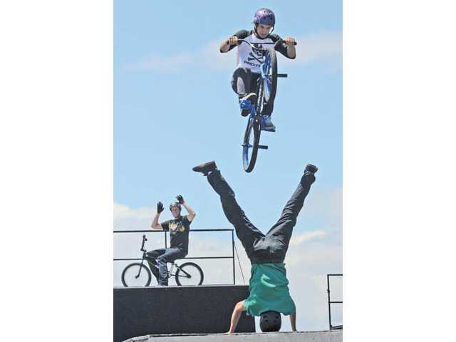 BMX rider Dan Norvell jumps over Ricky Vigil, foreground, as he does a handstand, while Joey Cordova, background, watches in the distance during a demonstration at the Valencia Kia dealership.