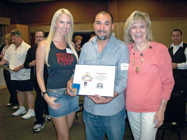 Winner of the third annual Soroptimist International of Santa Clarita Valley Fiesta Poker Tournament, Ramon Fabregas, of Valencia, center, is flanked by Tara Rice, tournament co-chairwoman, left, and Donna Kreutz, president of Soroptimist International of SCV, right.
