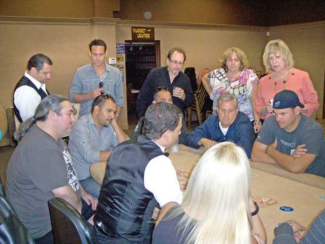 Spectators watch as the final table begins play at the third annual Fiesta Poker Tournament.