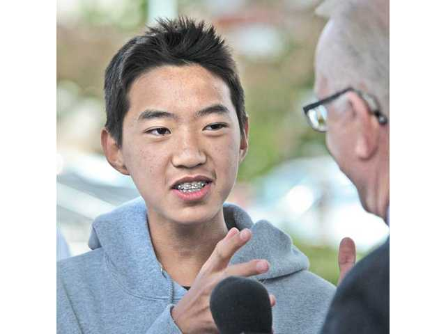 "William Oh, 14, left, a Golden Valley High School ninth-grader, discusses oil-company profits with Rep. Howard ""Buck"" McKeon, R-Santa Clarita, at the Chevron gas station in Valencia on Wednesday."