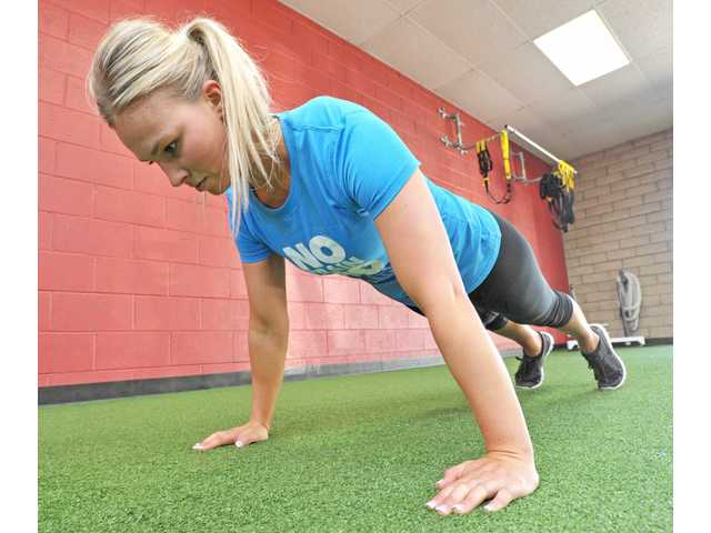 Charlotte Loa demonstrates the proper form for a pushup.