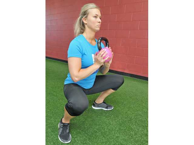 To perform a squat, start with your hands on your head, with good posture. Lower into a full range of motion squat. Add a dumbbell, or weight, to increase performance.
