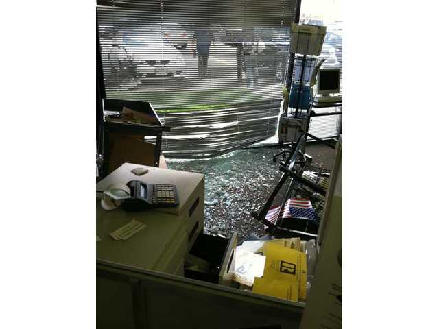 Security officers survey the damage caused when the driver of a Honda sedan smashed the car through the front window of the Southland Regional Association of Realtors' Canyon Country office Thursday afternoon. Nobody was injured in the crash that interrupted a real estate class and damaged equipment.