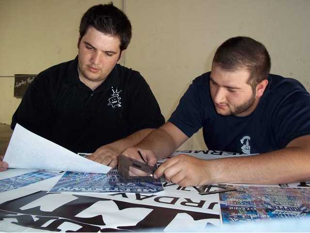 Golden Valley High School grad and former Yes I Can mentor Peter Yahiayan, left, and associate Steven Sagradyan work on the design of Summer Meltdown graphics at Yahiayan's Eye Finity Printing in Los Angeles.