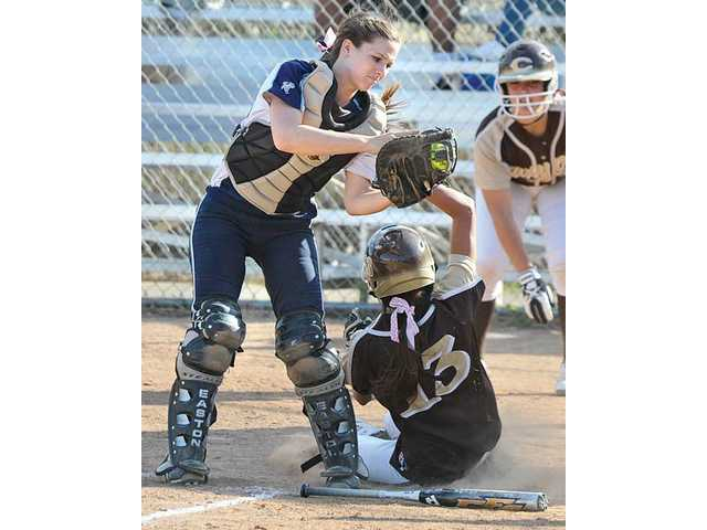 Saugus High catcher Karlee Bickford, left, tries to apply a tag on Canyon of Anaheim's Kaylenne McClure in the sixth inning on Thursday at Saugus High. Saugus lost 8-0.