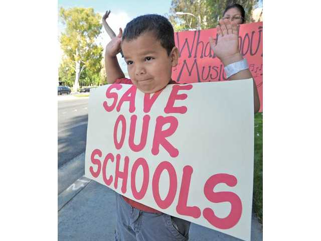 Second-grader Justin Mendez, 8, holds a sign as he joins his parents and teachers in front of City Hall in Valencia on May 13. The group was protesting state budget cuts to education.