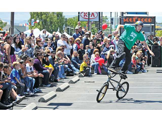 A crowd gathers to watch BMX bike rider Ricky Vigil perform at the Kia dealership at the inaugural Creekside Classic Car Show and Food Truck Festival on Creekside Road  in Valencia on Sunday.
