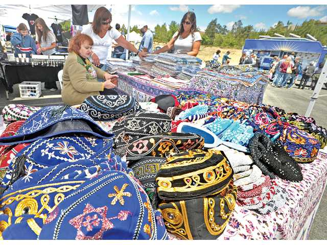Shelly Yekutiel, seated, Pam Fields, left, and Conzuelo Phippen lay out kova caps and Jewish tablecloths for sale at the SCV Jewish Food and Cultural Festival held in the College of the Canyons parking lot in Valencia on Sunday.