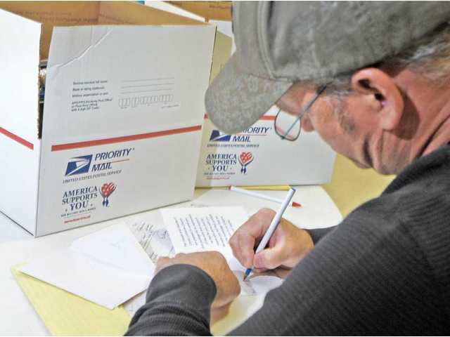 John Kniest, of Stevenson Ranch, writes a letter to be placed in a servicemen's care package at the Hands in Hearts care-package-boxing event held in the Fellowship Hall at Christ Lutheran Church in Valencia on Tuesday.