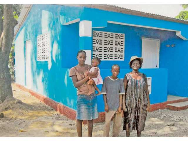 The Luckner Monestime Family from Chastenoye Cap-Haitian, Haiti, stands outside of their new home, which was paid for by a group of 74 Valencia High School students.