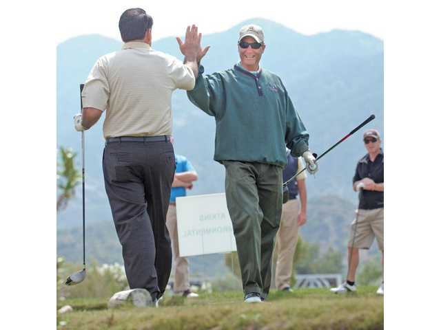 Tom Cole, left, and Mike Berger exchange a high-five after Coles drove off the first tee.