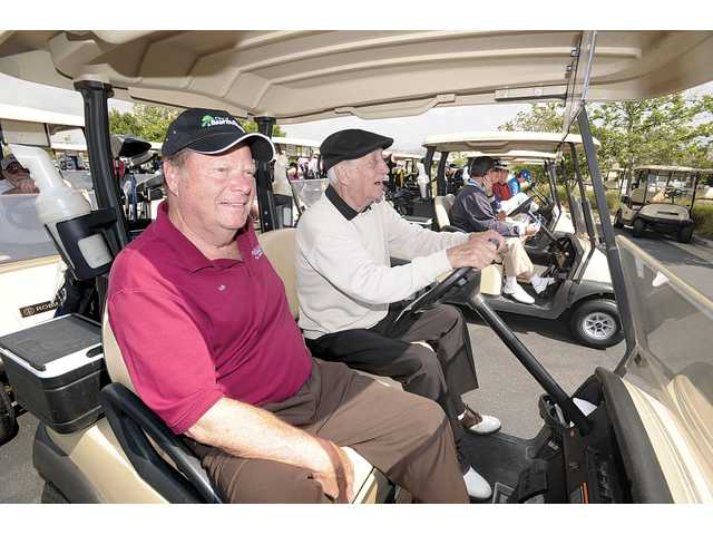Golfers Bob Kellar, left, and Mitch Davis prepare for the shotgun start. Kellar served as the honorary chairman of the tournament. Tournament co-chairwomen were Adele Macpherson and Sharon Langenbeck.