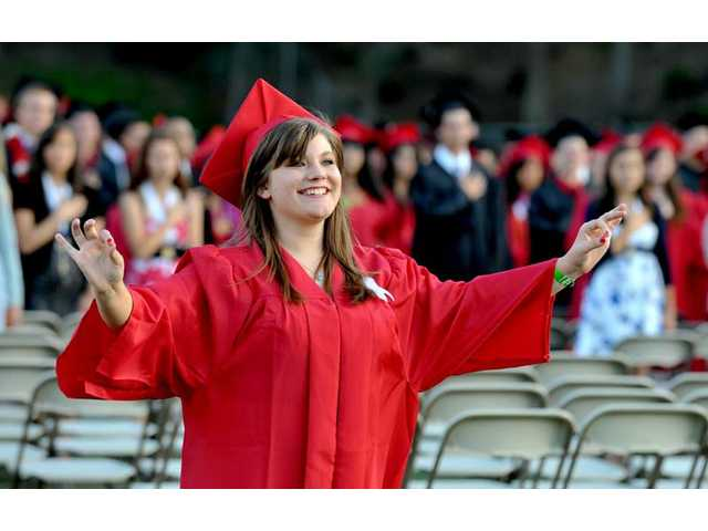 "Alixandria Barnum, 18, signs ""The Star-Spangled Banner,"" in American Sign Language at Hart High School's graduation ceremony at College of the Canyons on Wednesday."