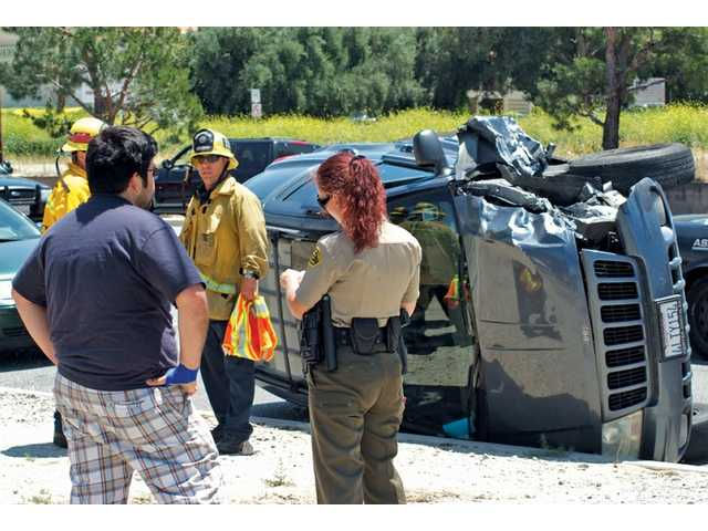 A Santa Clarita Valley sheriff's deputy takes a report from a man who witnessed a rollover crash on Soledad Canyon Road and Gladding Way in Santa Clarita on Thursday. Los Angeles County firefighters also responded.