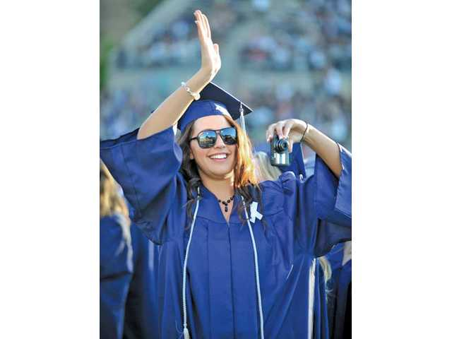 Brandi Mazzuca, 17, waves to the crowd during Saugus High School's graduation ceremony at College of the Canyons in Valencia on Thursday.