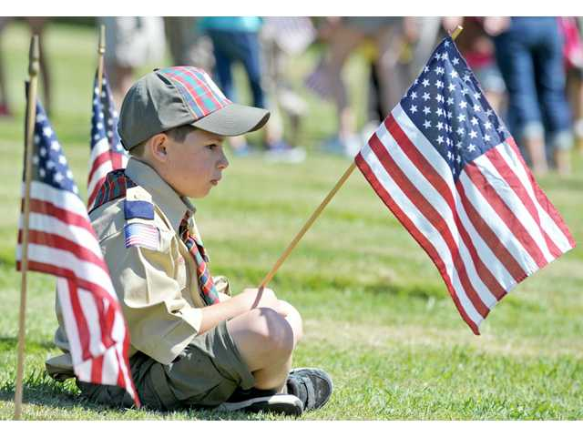 Jake Andrews, 9, a Webelos Scout of Valencia-based Pack 40, takes a break from placing American flags on graves.