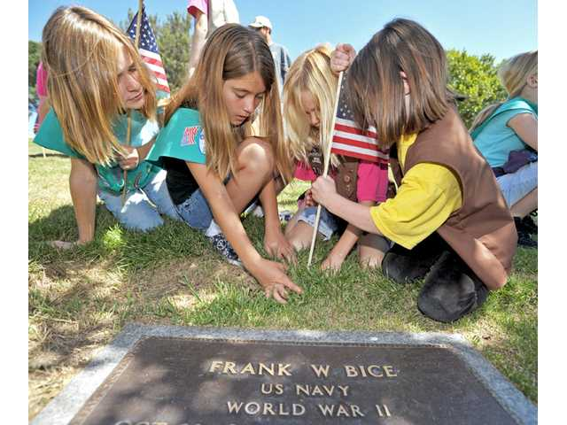 From left, Megan Hartmann, 10; Emily Fitzgerald, 10; Madison Hartmann, 8; and Shaya Wright, 7, help place an American flag on the grave of a veteran at Eternal Valley Memorial Park in Newhall on Saturday.
