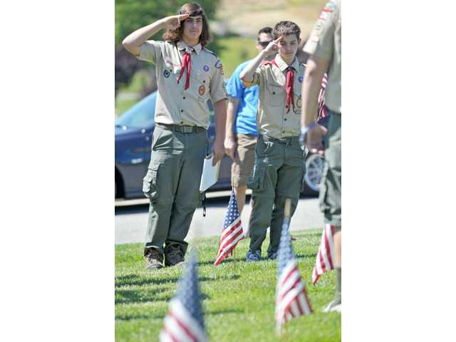 Patrick Sayegh, 16, left, and Alex Borsotti, 15, of Boy Scout Troop 609 salute after their group placed American flags.