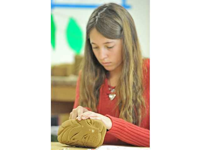Eighth-grader Sydney Hild, 14, sculpts a lion gargoyle sandstone at SCV International Charter School in Castaic on Tuesday. The project will be on display at the school's upcoming art festival.