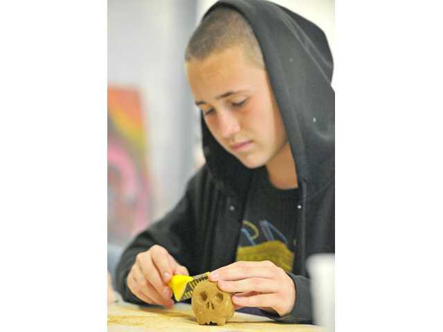 Ninth-grader Jace Bennett, 15, sculpts a skull gargoyle sandstone at SCV International Charter School in Casta