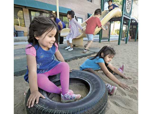Preschoolers Abigail Perez, left, and Madeline Chavez play in the playground at Kids Corner Preschool at The Child & Family Center in Santa Clarita on Wednesday as they wait for their parents to pick them up.