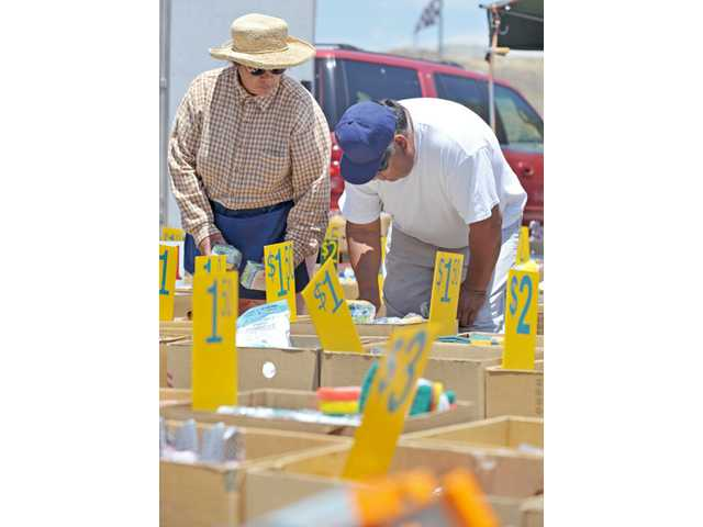Esther Rodriguez, left, assists a customer, who asked not to be identified, as he looks through housewares in the Santa Clarita Open Air Market at the Saugus Swap Meet in Saugus on Tuesday.