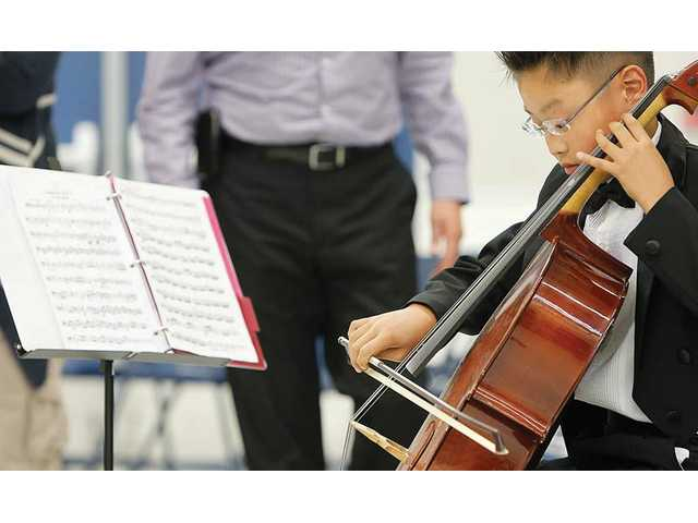 Maximus Chung, 11, of Stevenson Ranch Elementary School practices his cello prior to the start of Newhall School District's 33rd annual Spring Concert, which was held at Wiley Canyon Elementary School on Wednesday.
