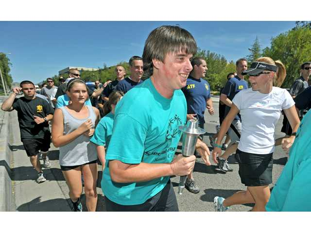 Sean Coskran, 25, carries a torch down Magic Mountain Parkway past the River Oaks Shopping Center in Valencia on Thursday, followed by Los Angeles County sheriff's deputies, sheriff's explorers and officers from the FBI, ATF and U.S. Secret Service, in the Law Enforcement Torch Run for Special Olympics.