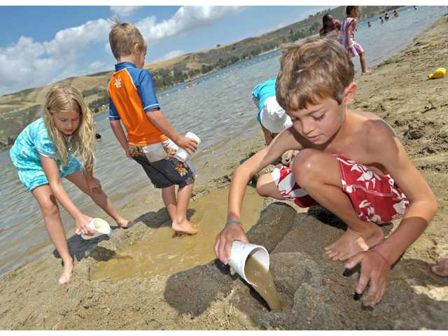 "From left, Rebekah Cooper, 9; Jesse Georgeson, 6; and Caleb Georgeson, 9, sculpt a ""spa"" in the sand in the north beach off the lower lagoon at the Castaic Lake State Recreation Area on Saturday."