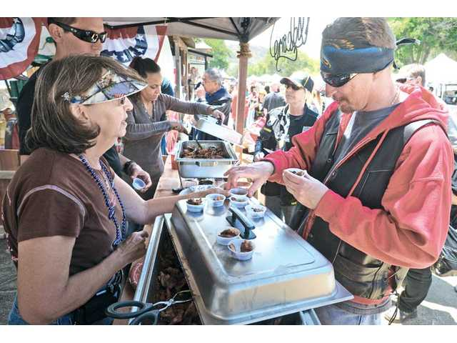 Jo-Ann Sorce, left, hands out samples  to Ron Minch, right, as he tastes the barbecue ribs, chicken and salsa  from the L.A. County Sheriff's Pitchess Detention Center maximum-security barbecue booth at the inaugural Stars and Stripes Barbecue and Salsa Showdown event held at Pitchess Detention Center's Jack Bones Equestrian Center in Castaic on Saturday.