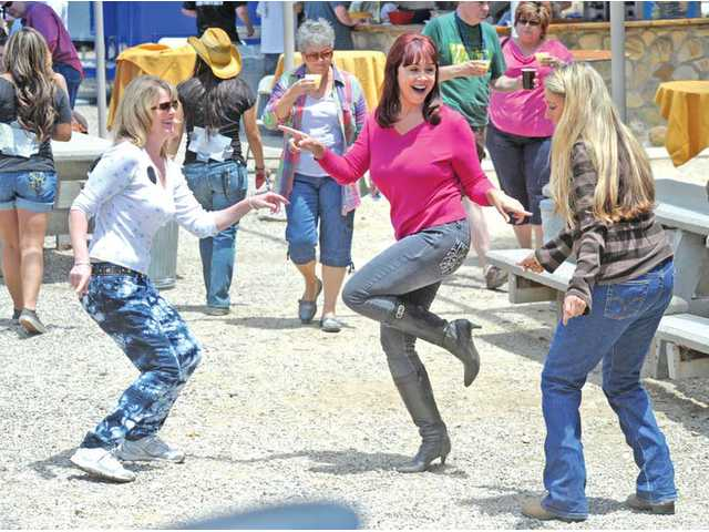 From left, Sharon Benner, Beverly Overstreet and Robin Holmwood dance to a Beatles song from the 1960s performed by The Tribute Band on Saturday.