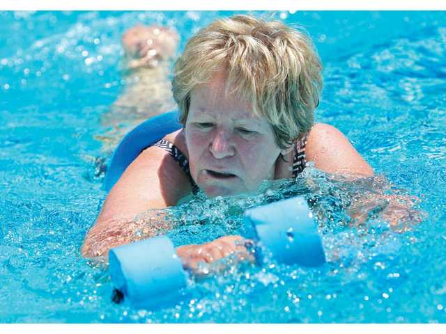 Nancy Spicer, of Canyon Country, swims with dumbbells down the length of the pool during the aqua aerobics class at the Santa Clarita Aquatics Center in Canyon Country on Wednesday.